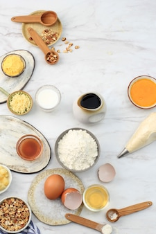 Various ingredients for baking preparation on marble table. flour, egg, cream, honey, cheese, and chopped almond ready to make baking mix batter