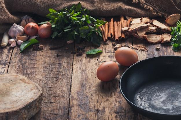 아시아 음식을 만드는 데 사용되는 다양한 재료가 나무 테이블의 팬 옆에 있습니다.