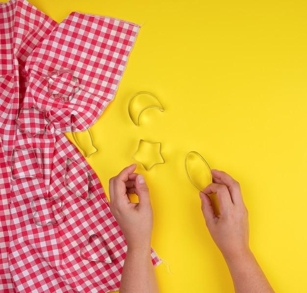 Различные железные формы для выпечки печенья в женских руках