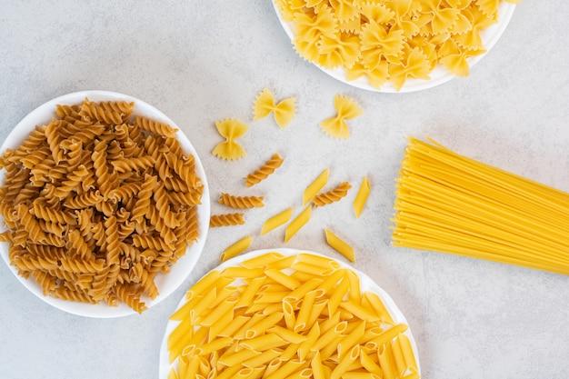 Разнообразная итальянская паста на мраморе.