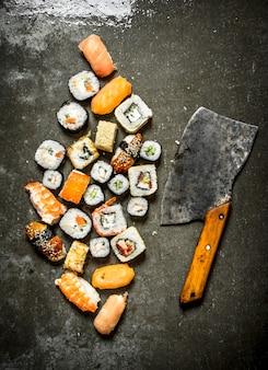 Различные японские суши-роллы с топором для нарезки. на каменном столе.