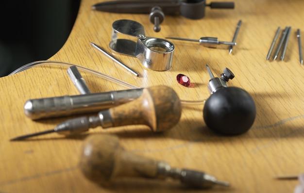 Различные инструменты ювелира на деревянном столе