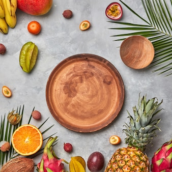 Various juicy exotic fruits, coconut, lychees, carom, pineapple, palm leaves and empty brown wooden plates on a gray concrete table