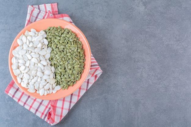 Vari chicchi in un piatto su un canovaccio, sulla superficie di marmo