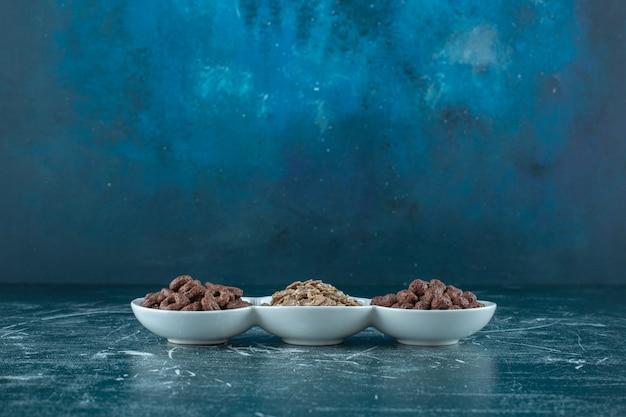 파란색 표면에 그릇에 다양한 아이 시리얼