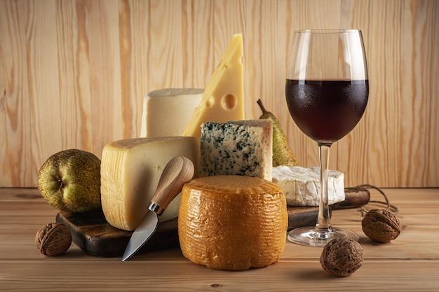 Различные виды сыра с бокалом вина на деревянном столе.