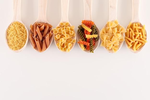 Различные виды макарон в деревянных ложках на белой поверхности с копией пространства