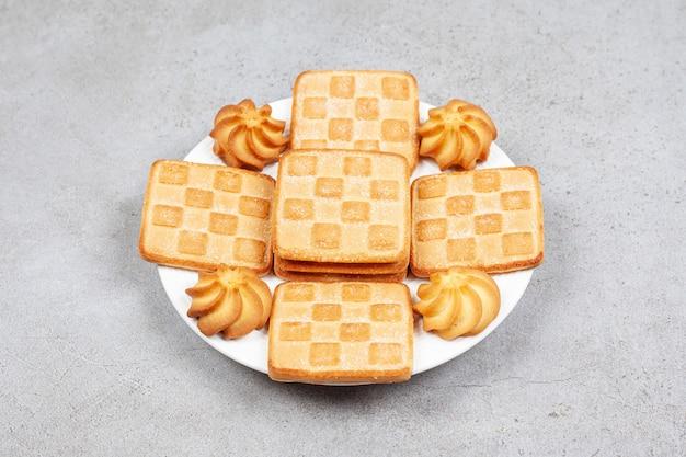 Vari tipi di biscotti sul piatto bianco sul tavolo grigio