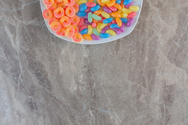 Various kinds of candies on white plate. top view.