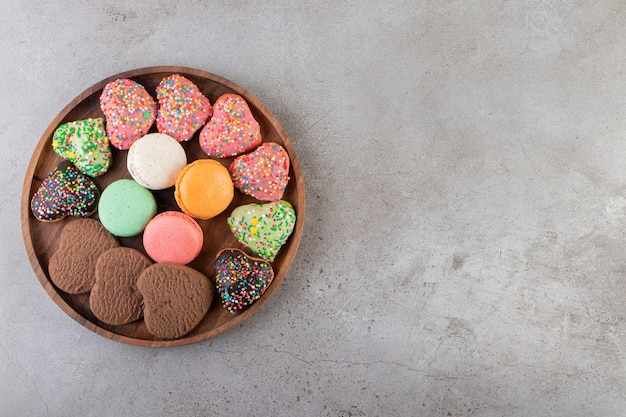 Various kinds of cookies on wooden tray on grey surface