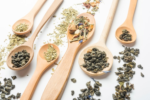 Various kinds of herbal tea in wooden spoons on white background