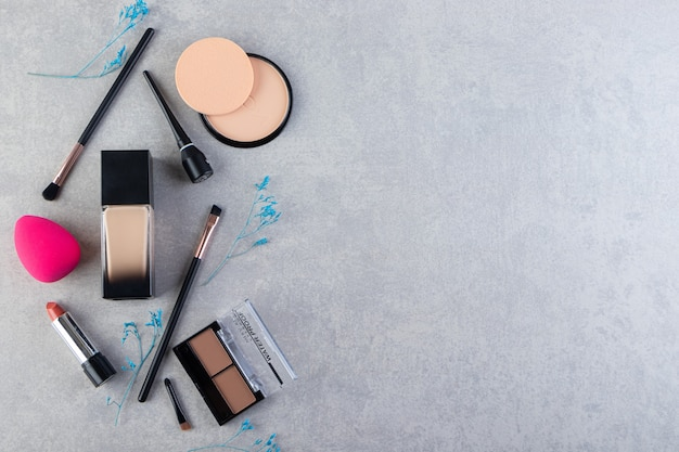 Various kinds if cosmetics products n grey background.
