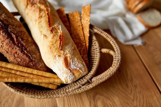Различные виды хлеба и хлебных палочек на деревянной поверхности