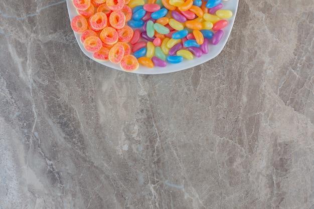 白いお皿にいろいろな種類のキャンディー。上面図。