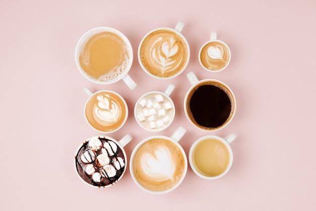 淡いピンクの背景にさまざまなサイズのカップに入ったさまざまな種類のコーヒー。コーヒータイムのコンセプト。フラットレイ、上面図