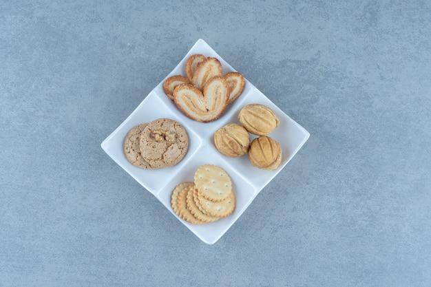 Различные виды печенья на белой тарелке на сером фоне.