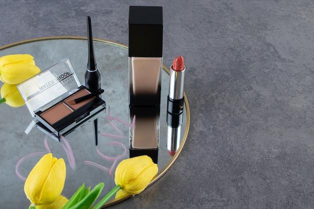 회색 배경 위에 거울에 있는 다양한 종류의 화장품.