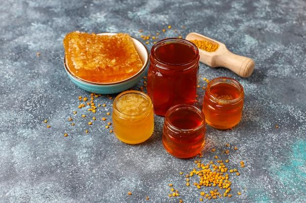 ガラスの瓶、ハニカム、花粉の蜂蜜の様々な種類。