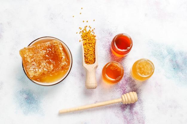 Различный мед в стеклянных банках, сотах и пыльце.