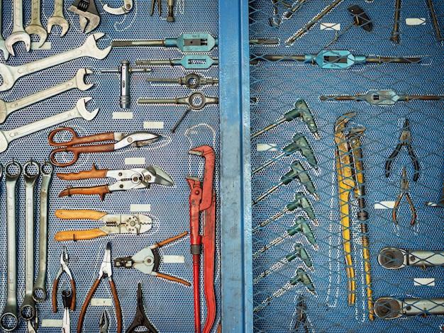 Различные виды механических инструментов висят в ящике для инструментов.