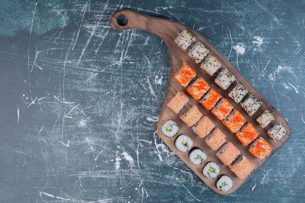 На деревянной тарелке подаются различные виды суши-роллов.