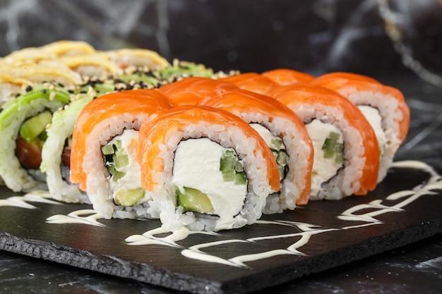 黒い大理石の背景にさまざまな種類の寿司を提供しています。日本料理の寿司メニュー。日本の寿司セット。マグロ、サーモン、エビ、カニ、キャビア、アボカドの巻き。横の写真。