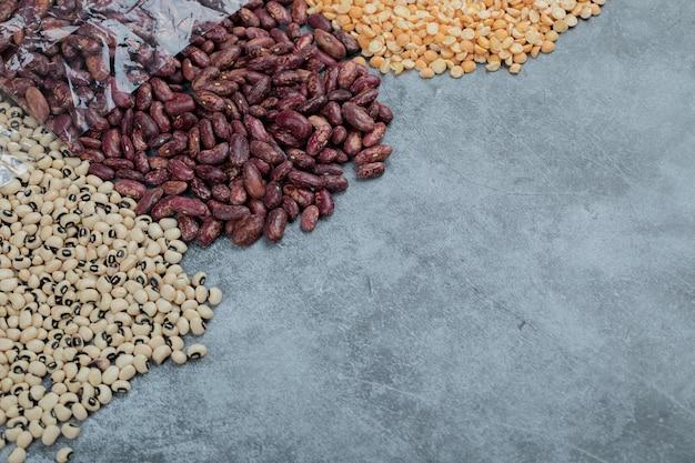 大理石の表面にさまざまな種類の未調理の豆。