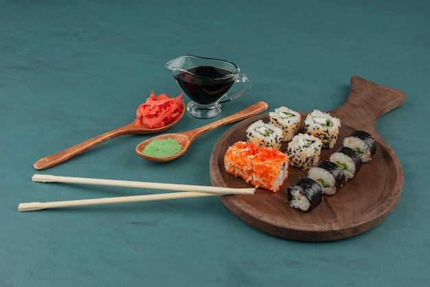 Различные виды суши-роллов с маринованным имбирем, васаби и соевым соусом на синем столе.