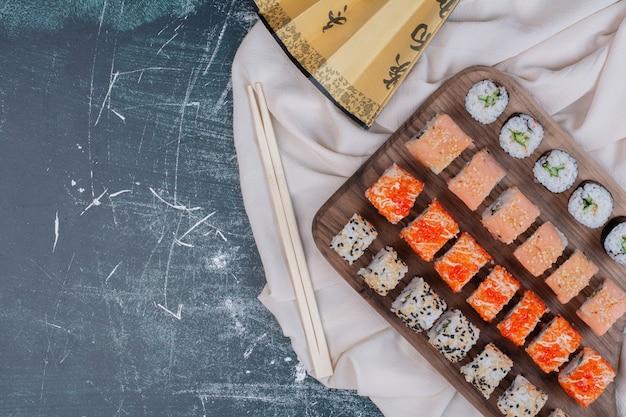 Vari tipi di involtini di sushi serviti su un piatto di legno con bacchette e ventaglio giapponese.
