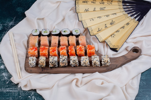 Various kinds of sushi rolls served on wooden platter with chopsticks and japanese fan.