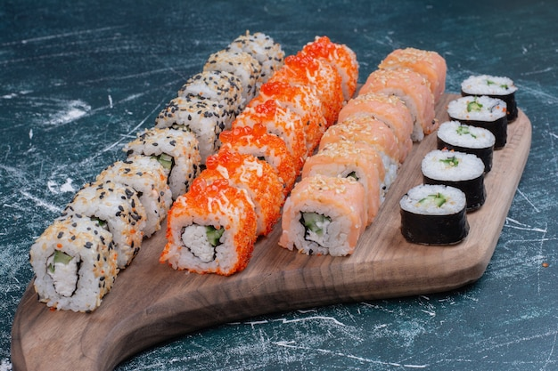 Various kinds of sushi rolls served on wooden platter.