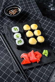 Various kinds of sushi served on black stone. black background. top view