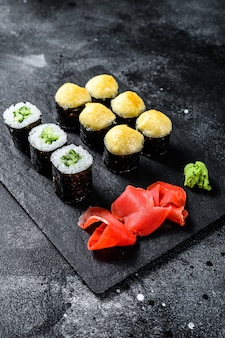 Various kinds of sushi served on black stone. black surface. top view