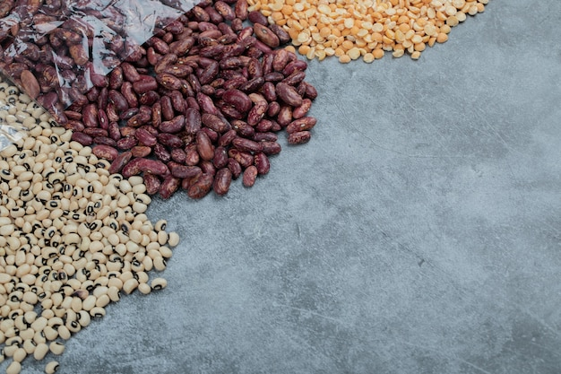 Various kinds of uncooked beans on marble surface.