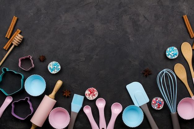 Различные кухонные принадлежности для выпечки. плоская планировка. вид сверху, макет рецепта на темном фоне.