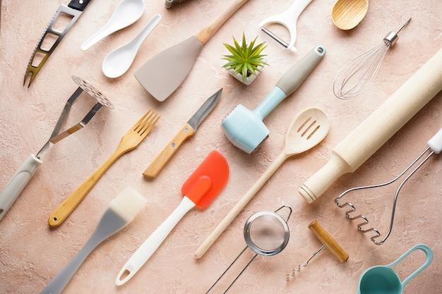 Различные кухонные принадлежности на бежевом фоне, вид сверху.