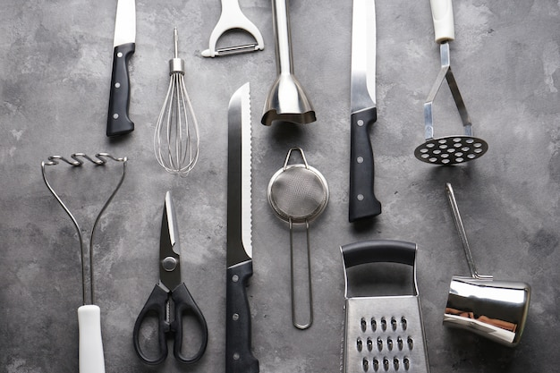 灰色のテーブルにさまざまなキッチン用品、フラットレイアウト。
