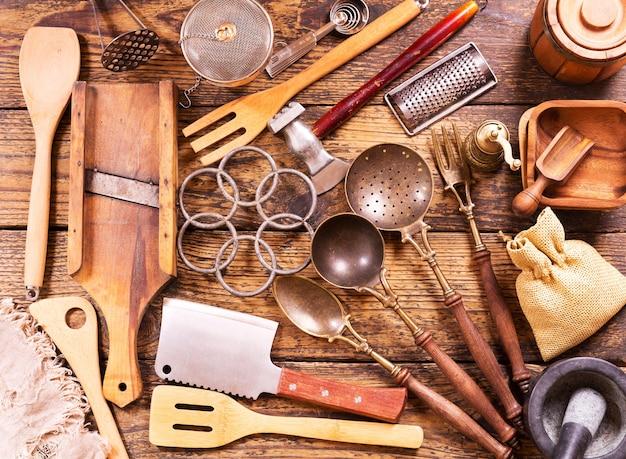 Различные кухонные принадлежности на деревянном столе, вид сверху Premium Фотографии