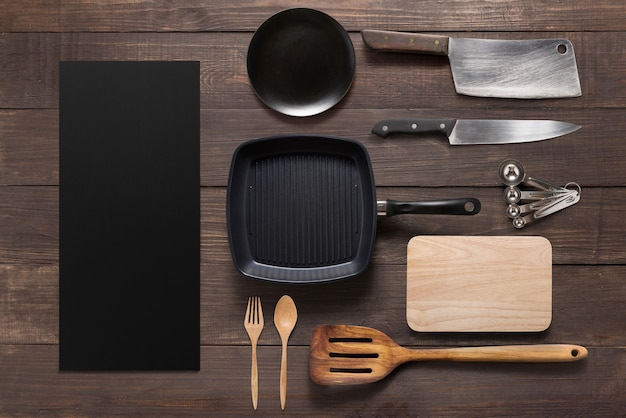 Various kitchenware utensils on the wooden background