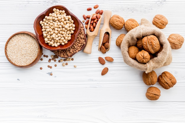 Various legumes and different kinds of nuts set up on white wooden table.