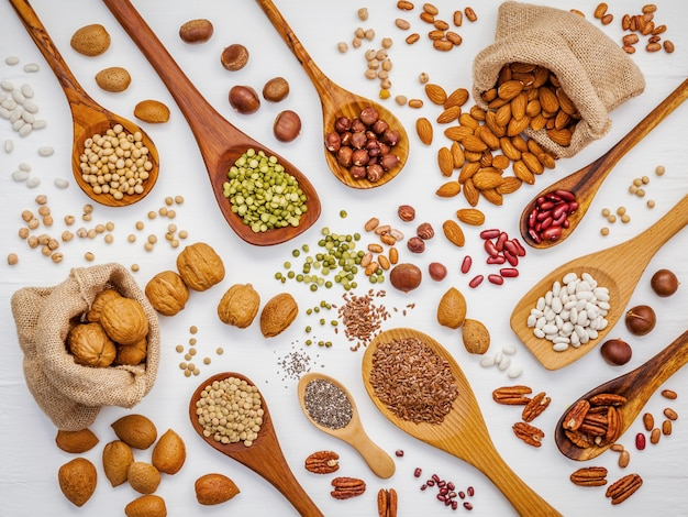 Various legumes and different kinds of nuts set up on wooden table.