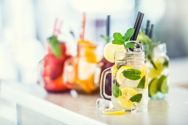 Различные лимонады в банках масона с апельсином, лаймом, лимонной клубникой и свежими фруктами.