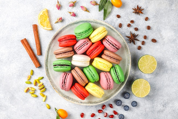 Various macaroons with pistachios, fruits, berries, coffee beans.