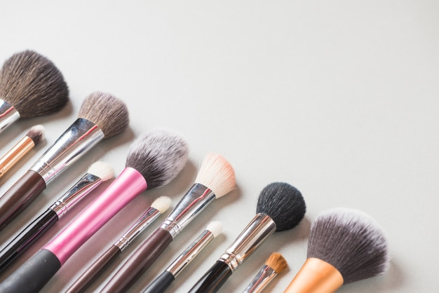 Various makeup brushes arranged in a row on white backdrop