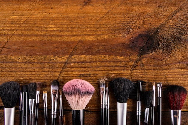 Various makeup brushes at the bottom of wooden background