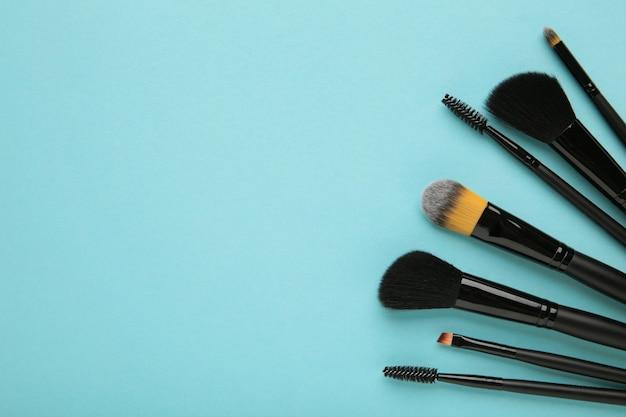 Различные кисти для макияжа на синем фоне с копией пространства. вид сверху