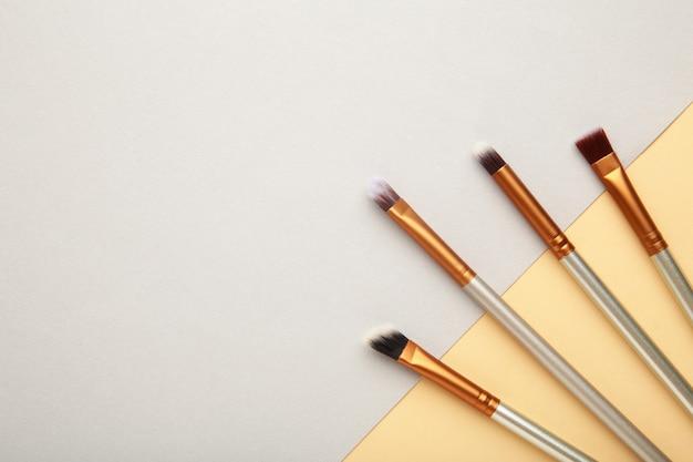 Различные кисти для макияжа на сером и бежевом фоне с копией пространства. вид сверху