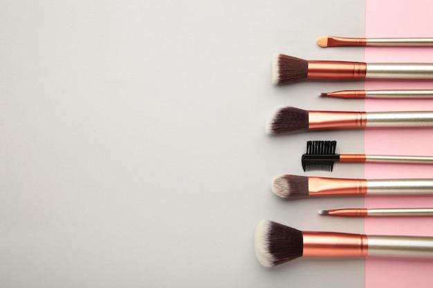 Различные кисти для макияжа на сером и розовом фоне с копией пространства. вид сверху