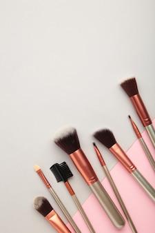 Различные кисти для макияжа на сером и розовом фоне с копией пространства. вертикальное фото