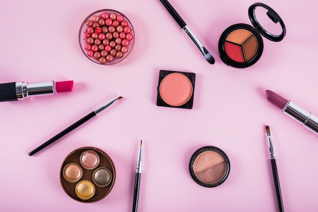 Various makeup and cosmetic products on pink backdrop